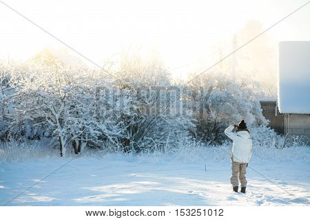 Elderly woman in warm clothes looking at her ancestors home on a cold and snowy winter morning