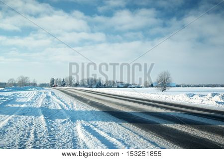 Asphalt road in snowy winter on beautiful frosty sunny day