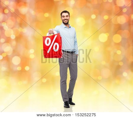 people, christmas, sale, discount and holidays concept - smiling man holding red shopping bags with percentage sign over lights background
