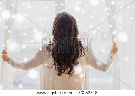 people, winter, christmas and hope concept - close up of happy woman opening window curtains at home over snow