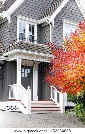 Beautiful upscale house in Canada with a Maple leaf tree next to the front door. Also available in horizontal.