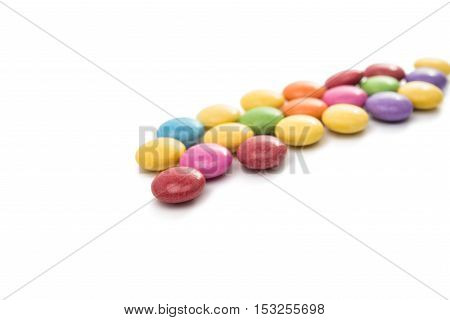 glazed multicolored chocolate pills on white background