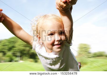 Close up portrait of little girl being spun in circles by her father at park outside