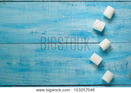 Fluffy white marshmallow on blue wooden table. Top view