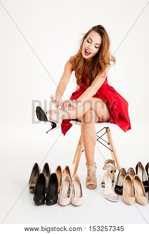 Portrait of a happy excited woman in red dress sitting and trying on her new high heels shoes over white background