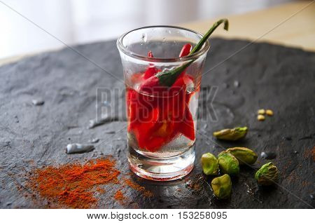 Vodka in shot glass with hot chili pepper