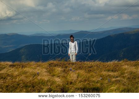 Handsome man bearded hipster with beard and moustache stands on mountain top on sunny summer day on cloudy sky