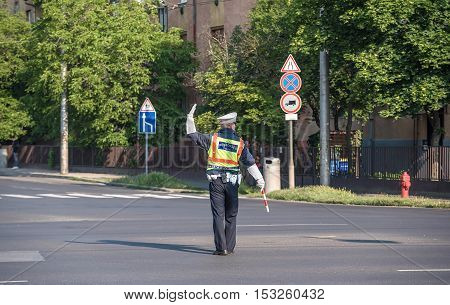 Traffic policeman directing cars in a crossing road detail