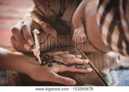 WADI RUM JORDAN - AUGUST 17 2016: unidentified bedouin making henna on a woman's hand. Hand decorations are usually done by a relative of the bride in her home