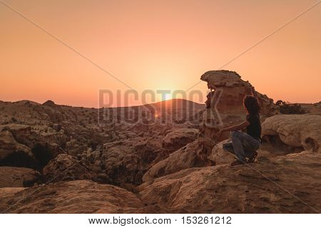 Petra, Jordan - 14 August 2016: unidentified boy enjoying sunset on the mountains near Petra Jordan after a trekking
