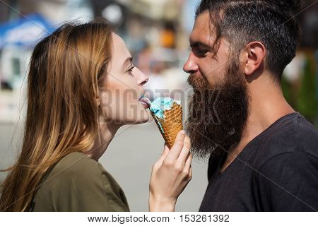 Couple of handsome bearded strong man with long beard and pretty sexy cute woman eating ice cream outdoor close up