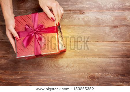 Female hands opening christmas or valentines day gift above wooden table. Top view with copy space