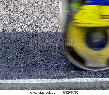 Compact steamroller flatten out the asphalt in motion.