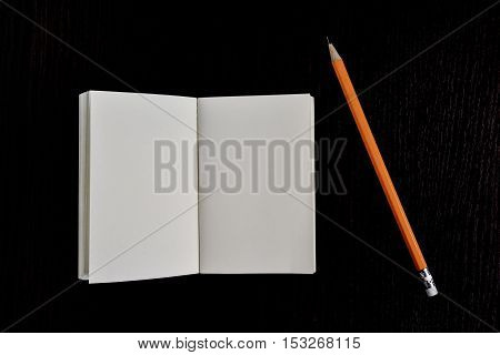 Open diary pocket book and pencil on black background mock up
