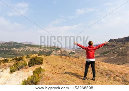 Tourist standing with outstretched arms and looking at the panoramic view in the majestic Golden Gate Highlands National Park travel destination in South Africa. Concept of adventure and traveling people.