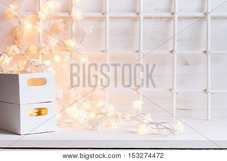Christmas soft home decor with lights burning and boxes on a white wooden background. Xmas background.
