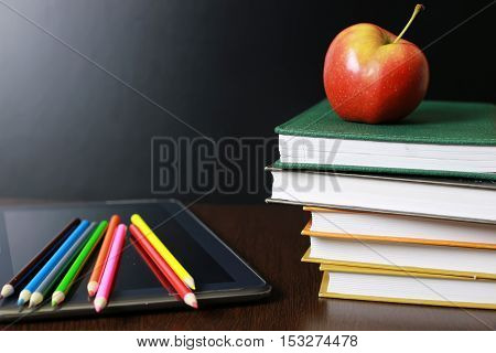 educational concept in the photos as a pile of books and a fresh apple as a source of vitamins for study