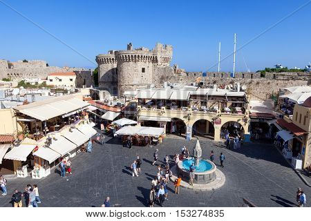 Rhodes, Greece - October 18, 2016: View of Rhodes old city center  square with restaurants and fountain, the old city of Rhodes is surrounded by aincent walls.