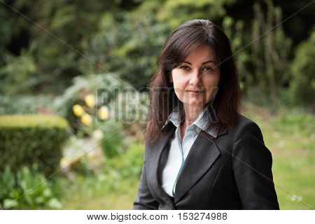 middle-aged woman in business suit in park