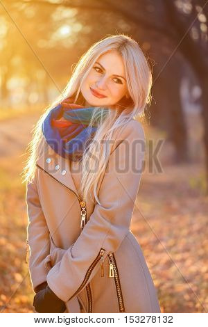 outdoors portrait of young blonde caucasian woman wearing autumn outfit outdoors in park on sunny fall day. Beautiful girl in beige coat and colorful scarf. Young woman in autumn park with sunshine