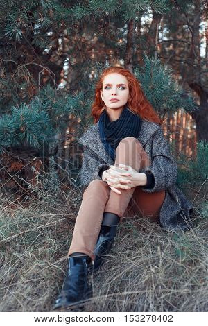 Beautiful red-haired woman. Redhead girl in autumn clothes in the forest. Redhead woman outdoor in autumn park weared scarf and coat. Autumn fashion look