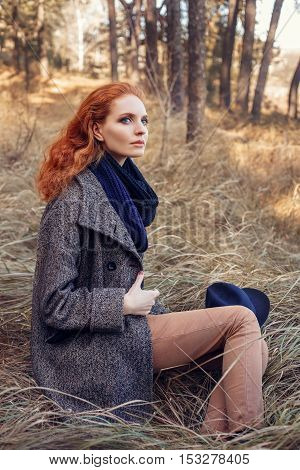 Beautiful red-haired woman. Redhead girl in autumn clothes in the forest. Redhead woman outdoor in autumn park weared scarf and coat. Autumn fashion look. Portrait of stylish woman with red hair