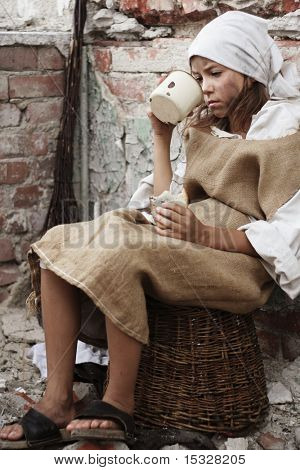 Small poor girl with a piece of bread and a mug in her hands. More available.