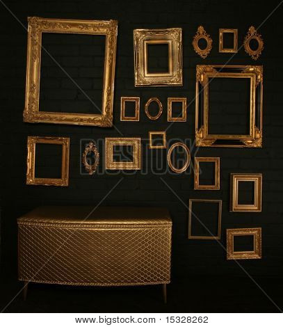 Gallery display - vintage gold frames and a chest on a black brick wall poster