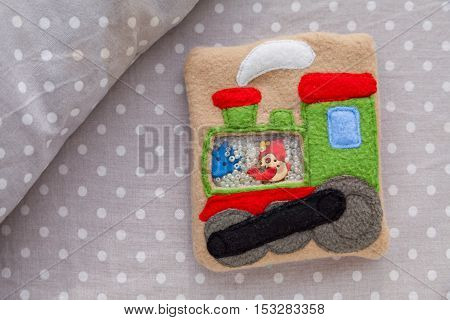 Children's soft toy locomotive made of colored fleece for motor development. Bag fleece filled with plastic beads and figurines on a background of gray fabric in white peas. handmade toys. Happy childhood.