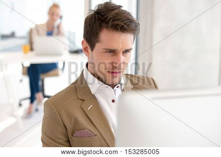 Young businessman using computer in new office