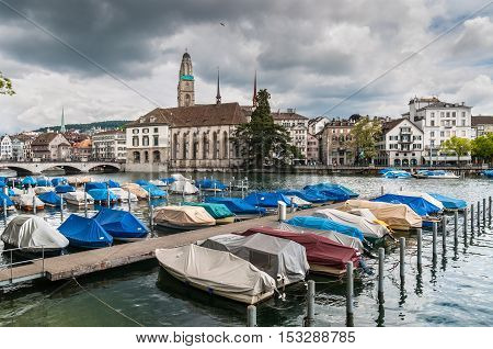 Zurich Switzerland - May 24 2016: View across the Limmat river to the Zurich Downtown in overcast rainy weather Switzerland. Boats in the foreground.