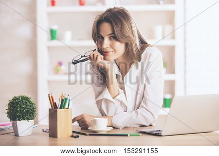 Portrait of charming caucasian businesswoman sitting at office desk with laptop coffee cup supplies and other items