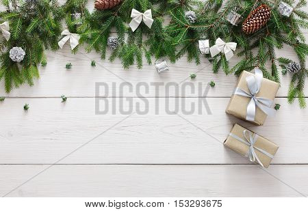 Christmas decoration, gift boxes and garland frame concept background, top view with copy space on white wood table surface. Christmas ornaments and presents border