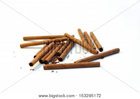 cigarillos and cigars chaotic stack on white background