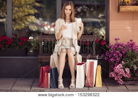 Woman with shopping bags sitting on bench. Urban life and shopogolic concept.