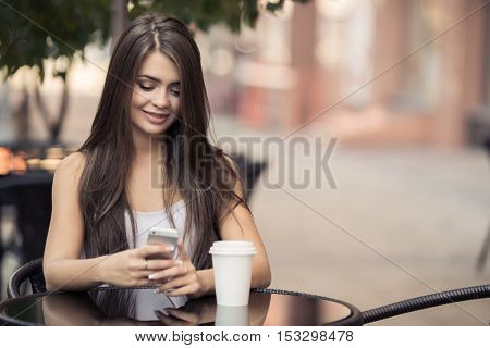 Young Beautiful Woman In Coffee Shop Sending Sms On Smartphone.