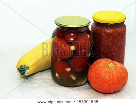 Homemade pickled tomatoes in jar and pumpkin. Autumn.