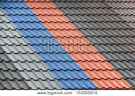 Architectural background. Texture of a metal roof tiles of black gray blue and red colors.