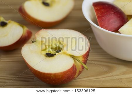 View on fresh and healthy Apples on a wooden board. Close-up of Fruits with a High Vitamin Contant for a healthy immune system. Sliced Red Apples