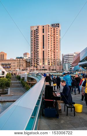 Adelaide Australia - September 11 2016: Man playing piano and people walking through Torrens foot bridge from Adelaide Oval after game in Adelaide city centre at sunset