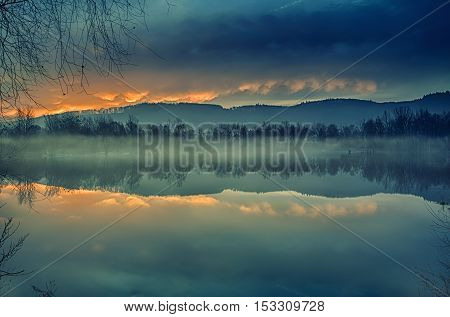 Reflection of trees from the water. Foggy sunrise. Autumn landscape on the lake.Tranquil landscape of misty swamp.Little island with trees.Mirroring the country from the river. poster