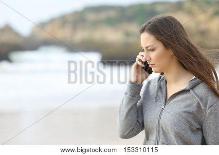 Sad teen talking on the phone on the beach