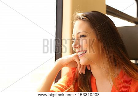 Happy train passenger traveling sitting in a seat and looking through the window