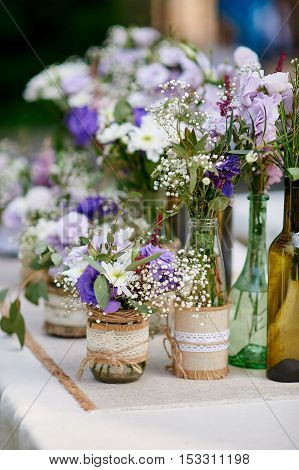 Rustic wedding decor, provence style. Lavender bouquet of field flowers and glass spice jars on wooden table.