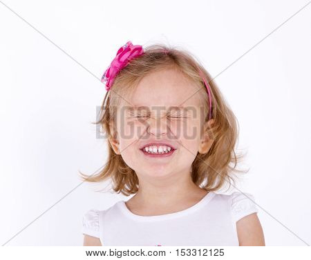 little girl close up strongly squeezed her eyes shut
