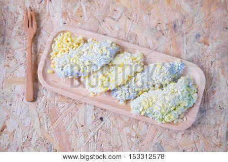 mung bean rice-crepe mock bean pods Thai dessert on wood tray