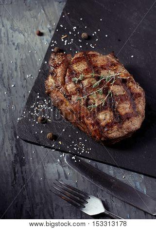 Closeup of medium rare roast beef steak with herbs pepper and salt