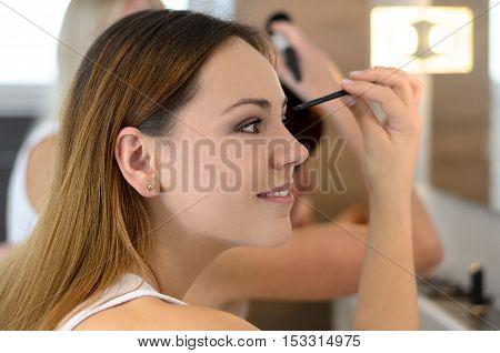 Pretty Young Woman Applying Mascara