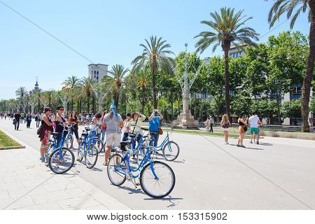 Barcelona, Spain - May 27, 2016: tourist group on bicycles on pedestrian alley in front of the Arc de Triomphe