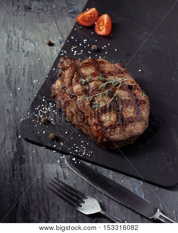Closeup of medium rare roast beef steak with herbs and tomato